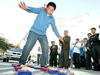 Zhang Xingquan pulling a car with his ears while walking on eggs